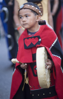 Max Wesley, 7, drums during a processional and grand entrance on Wednesday, June 8, 2016, near Juneau, Alaska. Celebration is a biennial festival of Tlingit, Haida and Tsimshian tribal members put on by the Sealaska Heritage Institute. (Photo by Rashah McChesney/KTOO)