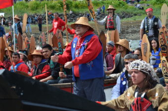 """John Martin asks for permission come ashore. He told the crowd, """"Today, we are practicing that our Tlingit, Haida, and Tsimshian people will come together. We will sing like one nation. We will speak like one nation. And we will dance like one nation."""" (Photo by Emily Kwong/KCAW)"""
