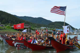 Tlingit master carver Wayne Price carved the two red canoes on the end.They joined the flotilla as they made their entrance into Douglas. (Photo By Emily Kwong/KCAW)