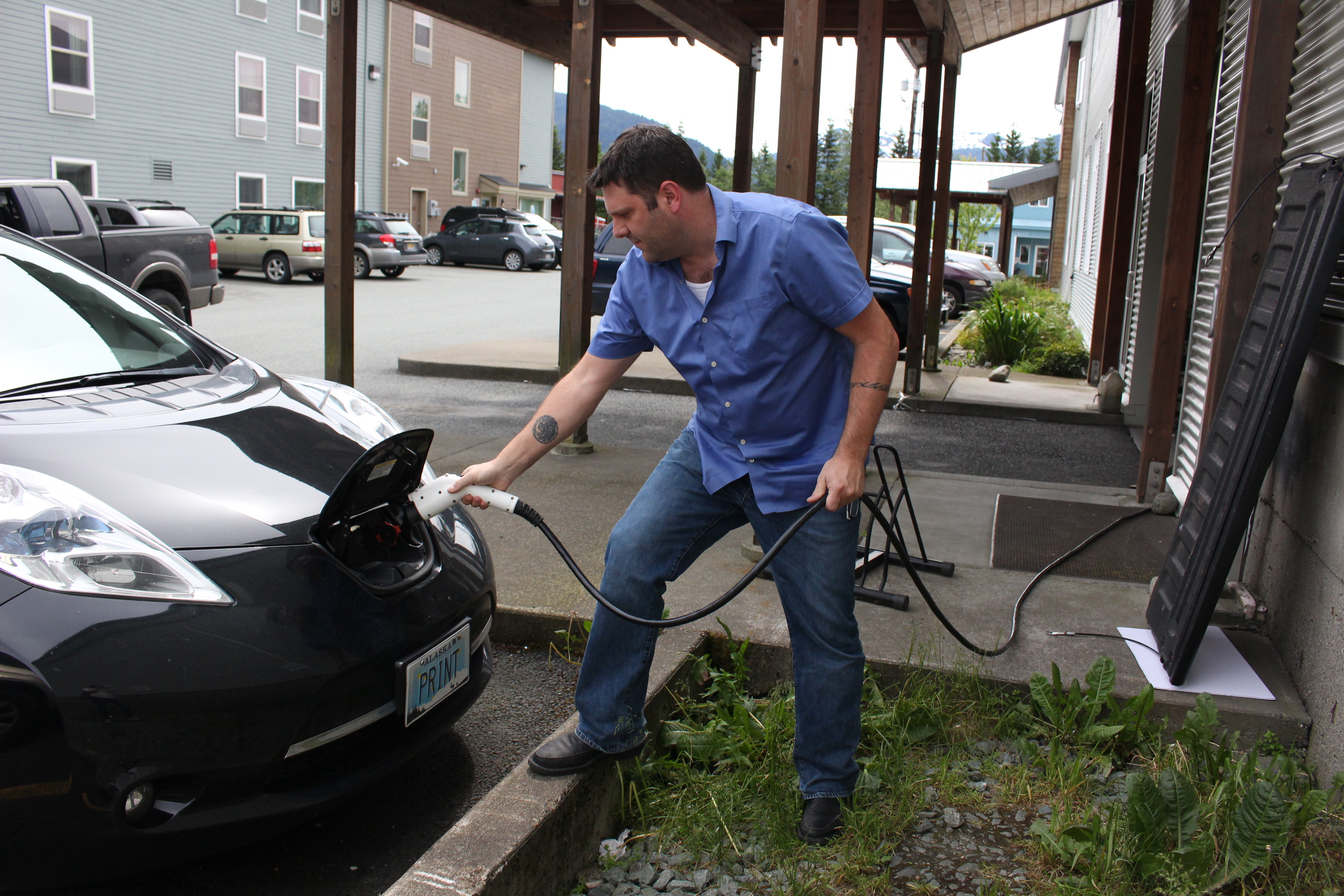 Travis McCain plugs in his 2013 Nissan Leaf. (Photo by Elizabeth Jenkins/KTOO)