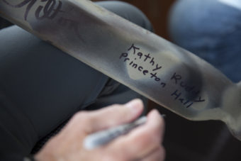 Kathy Ruddy, owner of the Princeton Hall, signs a ceremonial paddle on Wednesday, June 8, 2016, near Juneau, Alaska. Ruddy's boat was one of several that followed the One People Canoe Society group to provide safety and oversight during a trip from Juneau from Angoon. The group's landing on Douglas Island is the unofficial beginning of Celebration. (Photo by Rashah McChesney/KTOO)