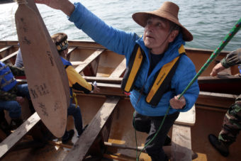 Ed Thomas, former President of the Central Council of Tlingit and Haida Indian Tribes of Alaska helps load a canoe before finishing a paddle from Angoon to Juneau on Wednesday, June 8, 2016, near Juneau, Alaska. The society began the trip on June 2. Their landing on Douglas Island is the unofficial beginning of Celebration. (Photo by Rashah McChesney/KTOO)