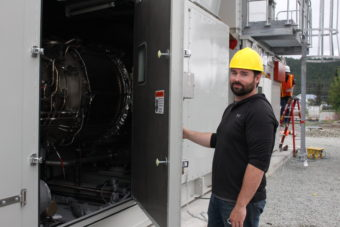 Bryan Farrell, an engineer at AEL&P, hold open the hatch the diesel fired turbine. (Photo by Elizabeth Jenkins/KTOO)