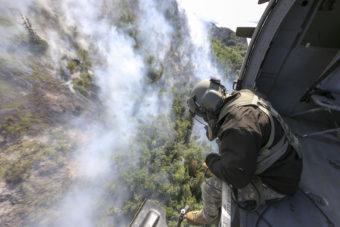 Staff Sgt. Steven Elliot, a crew chief with B Co., 1st Battalion, 207th Aviation Regiment, looks onto the McHugh Creek Fire during operations in support of wildfire suppression efforts near Anchorage, July 20, 2016. (Public domain photo by Staff Sgt. Balinda O'Neal Dresel/U.S. Army National Guard)