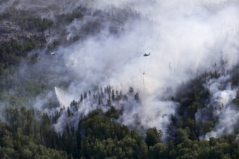 An Alaska Army National Guard UH-60 Black Hawk helicopter and a State of Alaska Division of Forestry helicopter dump several thousand gallons of water onto the McHugh Creek fire near Anchorage, July 20, 2016. (Public domain photo by photo by Staff Sgt. Balinda O'Neal Dresel/U.S. Army National Guard)