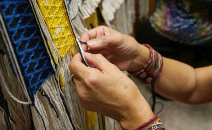 Clarissa Rizal's fingers dexterously manipulate the various colors of yarn Monday afternoon, August 22, 2016, as she works on the side borders of the Weavers Across Waters Chilkat/Ravenstail community robe. Rizal estimates that it takes her an hour to weave one inch of the side border, which means the robe is incredibly time intensive. (Photo by Tripp J Crouse/KTOO)