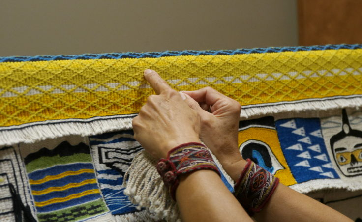 Clarissa Rizal points out details in the Weavers Across Waters CHilkat/Ravenstail community robe border Monday afternoon, August 22, 2016, at the Sealaska Heritage Institute, Juneau.