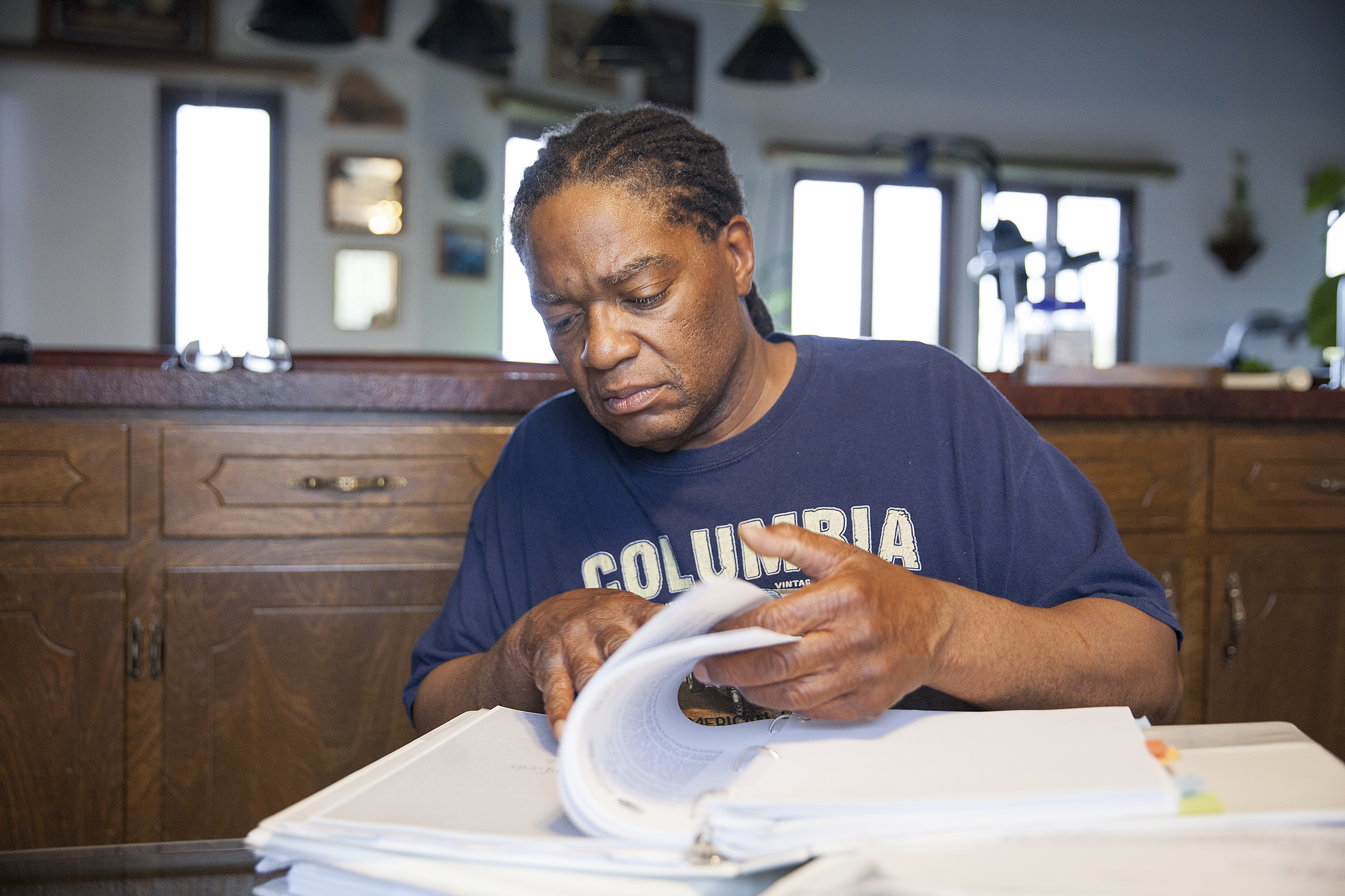 """Theodore """"Teddy"""" Burns looks through documents from his discrimination case at his home in Anchorage. Burns' appeal with the Ombudsman Office took eight years to complete. (Photo by Rashah McChesney/ KTOO)"""