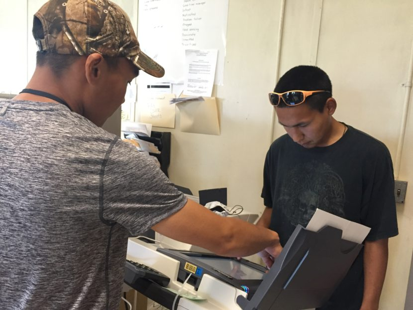 A poll watcher helps Newtok resident Bosco John, 27, vote during Tuesday's election. It was the village's first time using a digital machine. (Photo by Mareesa Nicosia, The 74)