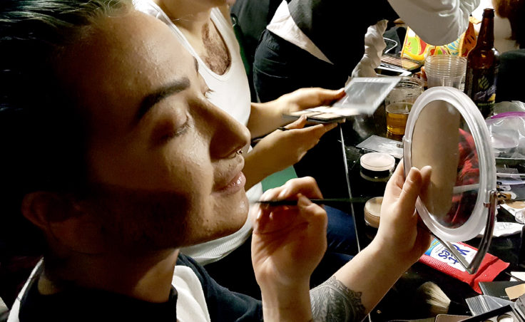 Stephanie Davis applies a stippling makeup effect to her jawline to create the illusion of facial hair stubble. Davis, who portrayed Stevie Smalls, one of the drag kings in the Femme Fatale show Friday at Rendezvous in downtown Juneau. (Photo by Tripp J Crouse/KTOO)