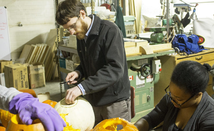 Sam Bornstein works on his pumpkin, which featured a flaming skull pattern on Monday during Juneau Makerspace's weekly open studio night. Bornstein is the group president. KTOO's Lakeidra Chavis also participated in the pumpkin carving. (Photo by Tripp J Crouse/KTOO)
