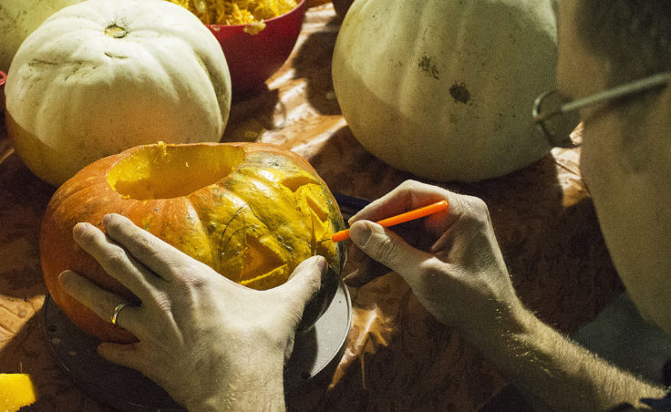 Keith Karpstein uses a small knife to carve the face of a jack-o'-lantern out of his pumpkin on Monday at Juneau Makerspace in Lemon Creek. (Photo by Tripp J Crouse/KTOO)