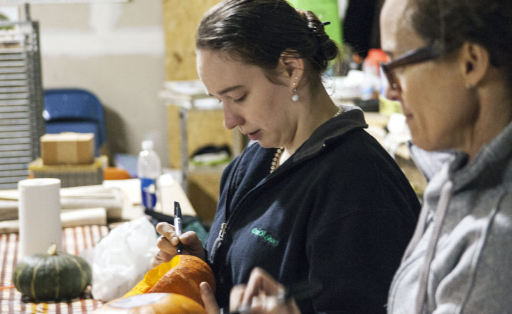 Arielle Parker Fargnoli draws a pattern on her pumpkin while chatting with the group Monday night at Juneau Makerspace. (Photo by Tripp J Crouse/KTOO)