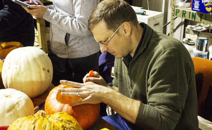 Keith Karpstein holds his pumpkin steady as he carves eye holes into his jack-o'-lantern on Monday at Juneau Makerspace. (Photo by Tripp J Crouse/KTOO)