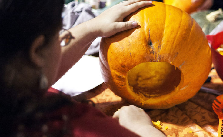 Grace Amundsen scrapes the guts out of her pumpkin in preparation for her design. Amundsen is the Juneau Makerspace event coordinator. (Photo by Tripp J Crouse/KTOO)