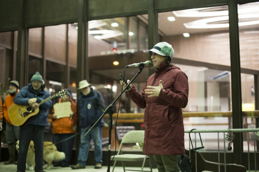 A woman in a red jacket and blue had speaks at a rally outside the Juneau Federal Building