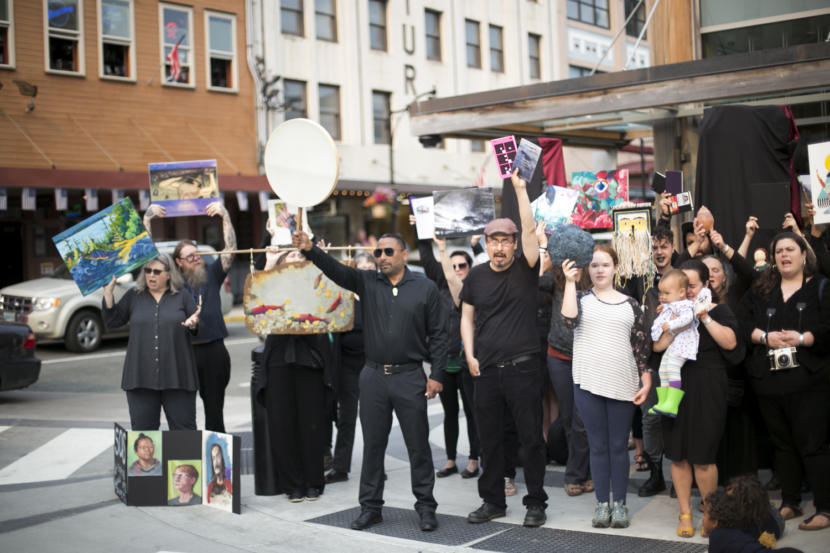 People dressed in black hold up paintings, books, drums, and artwork on a street corner in Juneau. Juneau artists hold up their work at a demonstration outside Sealaska Heritage Institute protesting the budget cuts to the Alaska State Council on the Arts on Tuesday, July 9, 2019. (Photo by Annie Bartholomew/KTOO)