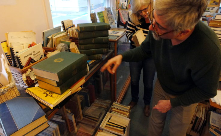 Leslie Longenbaugh and John Longenbaugh survey a set of books for a customer at Observatory Books.