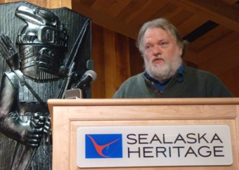 The Alaska State Museum's Steve Henrickson discusses Tlingit armor during a Dec. 1, 2016, lecture at the Walter Soboleff Building. To the left, Preston Singletary's house pole depicts an armored warrior. (Photo by Ed Schoenfeld/CoastAlaska News)