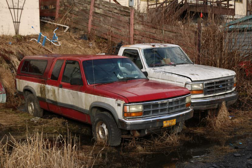 Old trucks are parked in the bushes in Wrangell. The Southeast city is one of eight working on a group agreement to collect and barge old vehicles and other scrap metal south for recycling. (Photo by Aaron Bolton/KSTK)