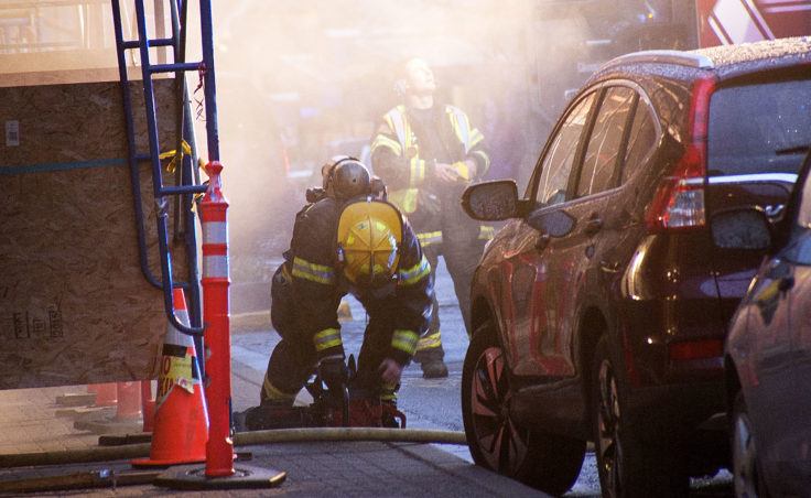 A firefighter attempts to start a chainsaw Saturday night, April 15, 2017, amid smoke coming from a fire in the 200 block of Seward Street, downtown Juneau. (Photo courtesy Tripp J Crouse)