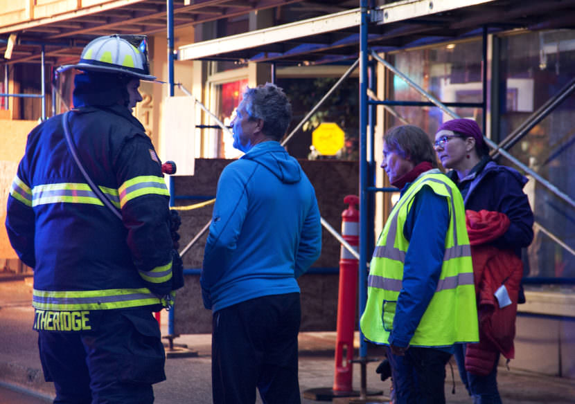 A firefighter talks with store owner Art Sutch on Saturday night, April 15, 2017, as emergency personnel work the scene of a fire in the 200 block of Seward Street, downtown Juneau. (Photo courtesy of Tripp J Crouse)