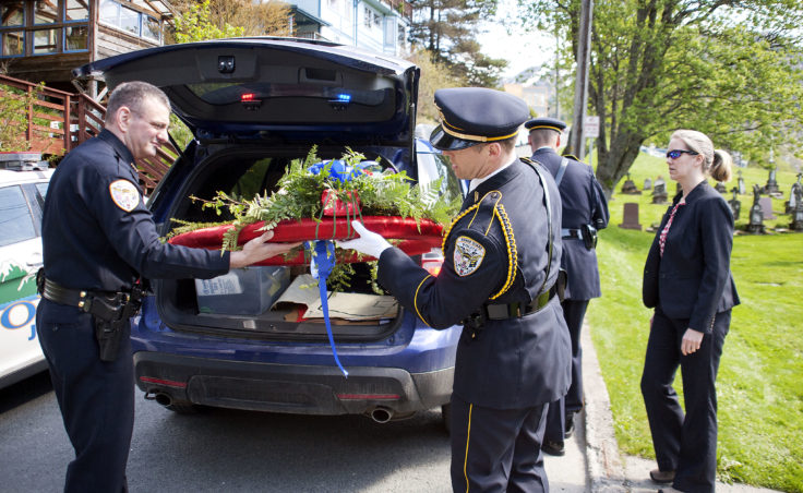 Juneau Police Chief Bryce Johnson helps police Sgt. Krag Campbell unload a wreath Wednesday, May 10, 2017, at Evergreen Cemetery, Juneau, during a memorial ceremony at the grave site of Traffic Officer Richard Adair, who was shot and killed in 1979. (Photo by Tripp J Crouse/KTOO)