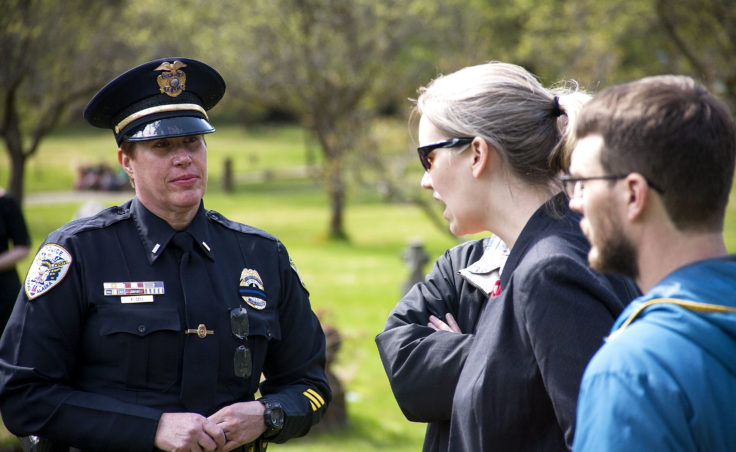 Juneau Police Lt. Kris Sell, left, talks with Sarah Hieb and Rob Heide on Wednesday, May 10, 2017, after the memorial service at Evergreen Cemetery, Juneau. (Photo by Tripp J Crouse/KTOO)