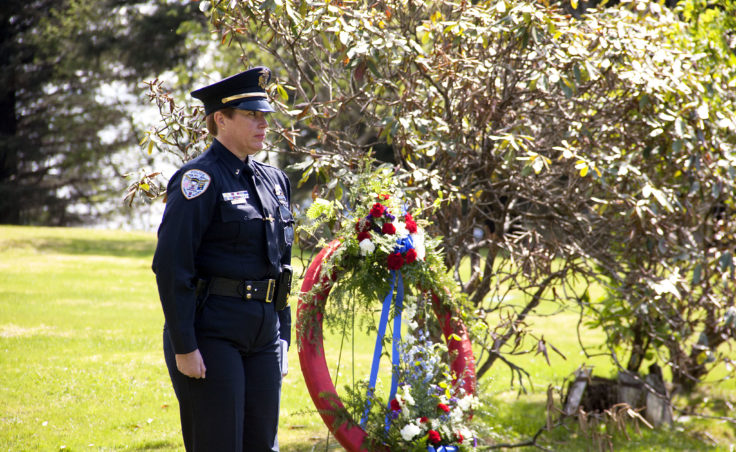 Juneau Police Lt. Kris Sell stands at attention Wednesday, May 10, 2017, during a memorial service and wreath laying at the grave site of Traffic Officer Richard Addair, who was shot and killed in 1979. (Photo by Tripp J Crouse/KTOO)