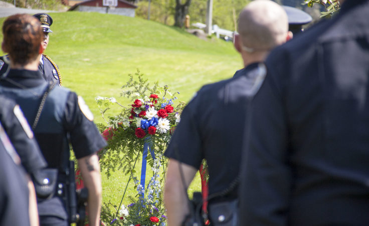 Juneau Police place a wreath Wednesday, May 10, 2017, during a memorial ceremony at the grave site of Traffic Officer Richard Adair, in Evergreen Cemetery, Juneau. (Photo by Tripp J Crouse/KTOO)