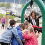 Miss Alaska USA Alyssa London pushes Juneau Community Charter School students on playground equipment on Thursday, May 25, 2017, at Sandy Beach.