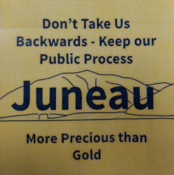 Anti-mining critics handed out stickers like these at a City and Borough Juneau Assembly committee meeting