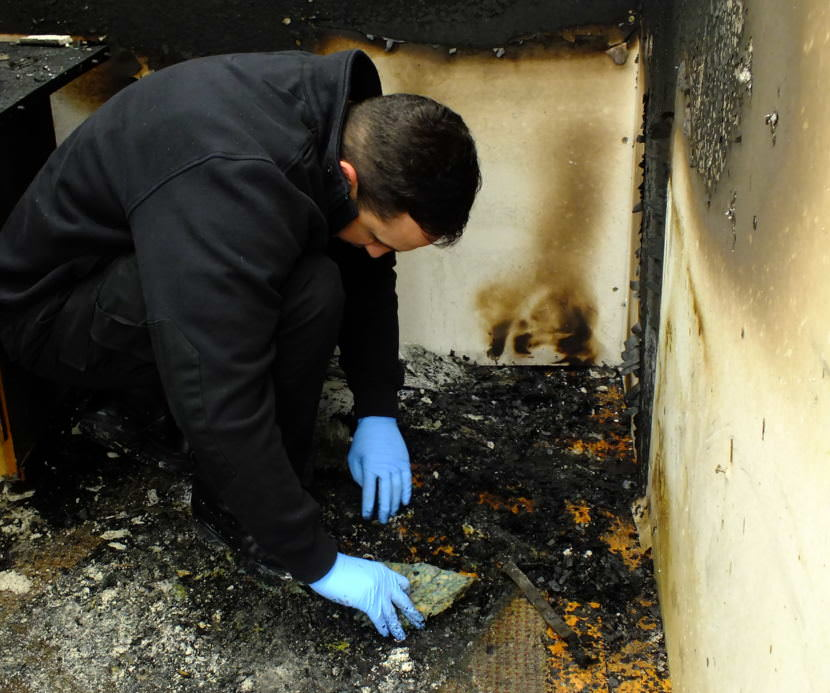 A student investigator sifts through debris and checks the underside of a carpet for a possible accelerant during a fire investigator training exercise at Juneau's Hagevig Regional Fire Training Center in 2017. (Photo by Matt Miller/KTOO)