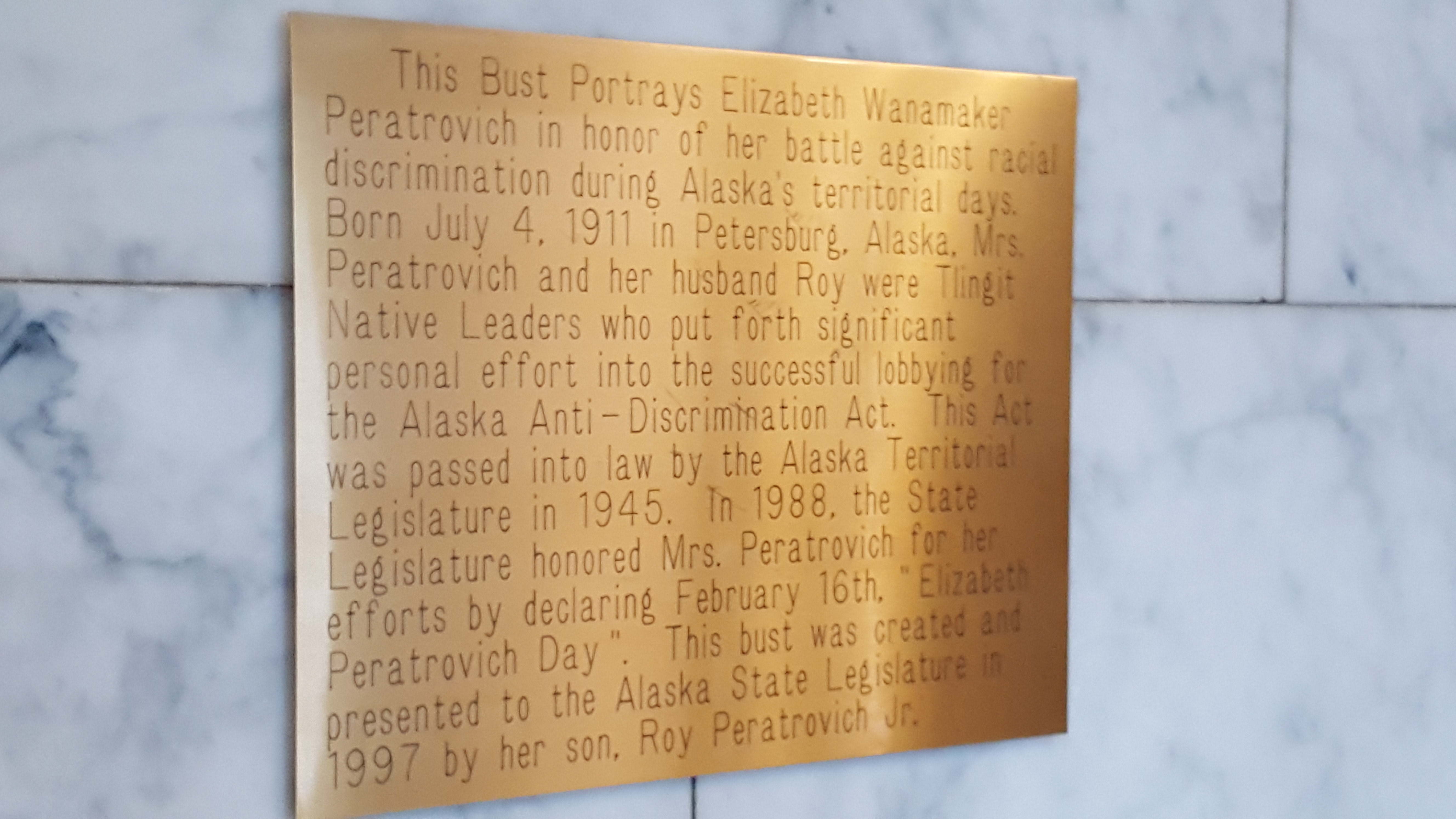 A plaque explains the importance of Elizabeth Peratrovich and the Anti-Discrimination Act of 1945 above a bust of the Alaska Native civil rights leader in the Alaska Capitol in downtown Juneau. (Photo by Tripp J Crouse/KTOO)