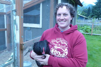 Sarah Dolan stands in front of her run and chicken coop holding a chicken on Saturday.