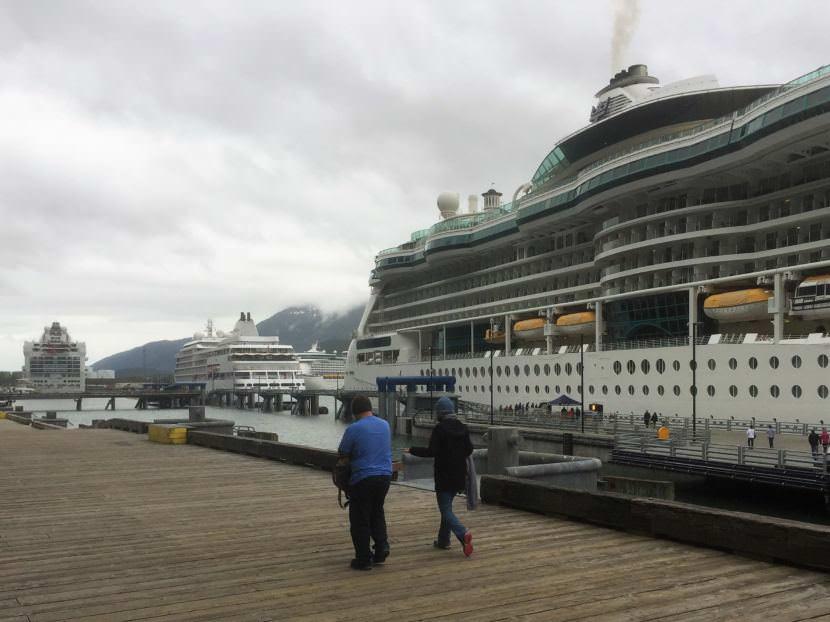 Passengers walk a downtown Juneau dock where three cruise ships are tied up June 11, 2017. (Photo by Ed Schoenfeld/CoastAlaska News)