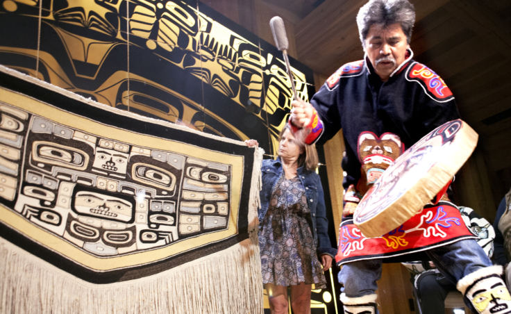 Yeilnaau Joe Zuboff calls for the spirits of a 100-plus-year-old Chilkat robe to return home Aug. 26, 2017, during a homecoming ceremony in the Shuka Hit clan house in downtown Juneau's Walter Soboleff Building. Gretchen Jacobsen, who with her husband donated the robe to Sealaska Heritage Institute, watches as Brian Katzeek dances behind the robe.