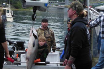 A family watches from their boat as Kami Bartness weighs one of their fish on a hanging scale at a float in the Auke Bay harbor.