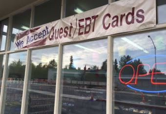 A sign outside of a store in midtown Anchorage announcing that they accept EBT Cards, the distribution method for SNAP benefits. (Photo by Hillman/Alaska Public Media)