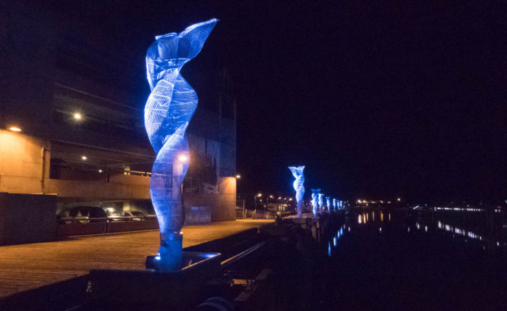 Nighttime, looking down a row of 20 foot tall metal sculptures mounted on the edge of a dock and lit up with bright blue light. The sculptures are made of many thin strands of metal swirling around a central core from the base to the top.