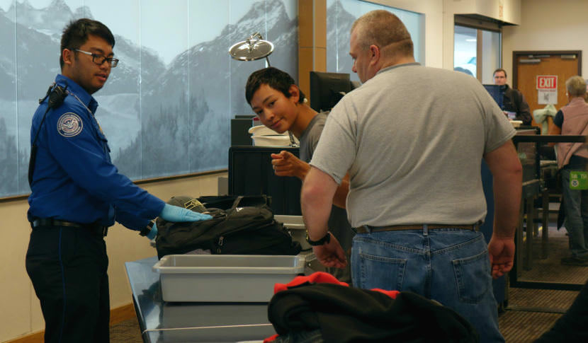 Transportation Security Officer Renier Cava preps passengers' carry-on belongings for X-ray screening at Juneau International Airport on Wednesday, Oct. 11, 2017.