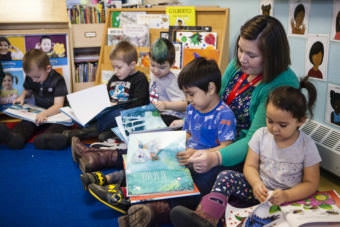Tlingit & Haida Head Start teacher Kayla Tripp and her class look through six new Baby Raven Reads books Oct. 20, 2017, after they were delivered by Sealaska Heritage Institute staff. (Photo by Nobu Koch/courtesy Sealaska Heritage)