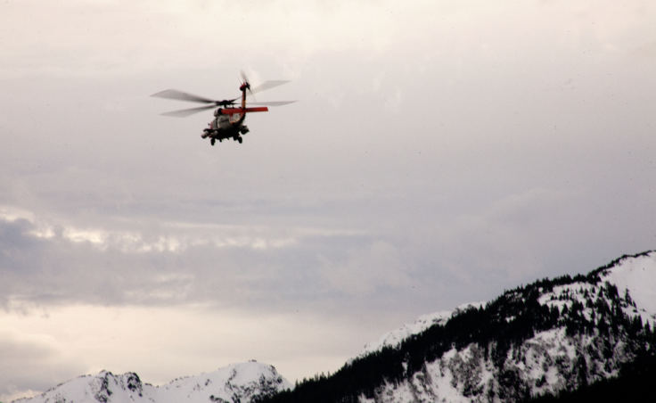 A Coast Guard H-60 helicopter flies down Gastineau Channel on Wednesday, Dec. 6, 2017, during the search for two men who went missing after a boat capsized the night before near Aurora Harbor. (Photo by Tripp J Crouse/KTOO)