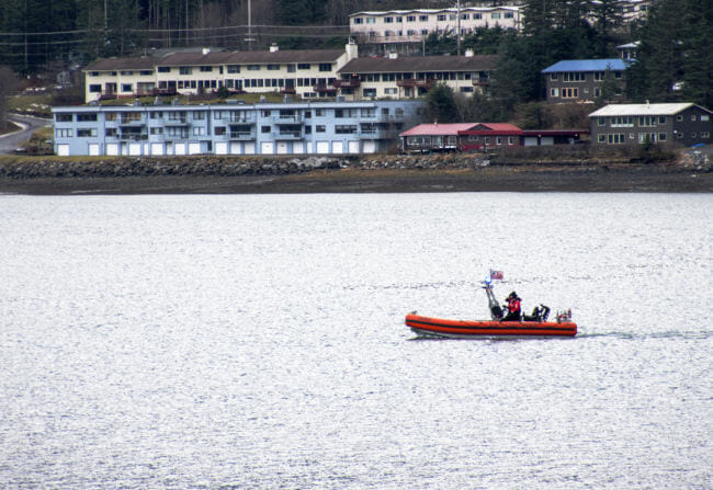 The Coast Guard searches Gastineau Channel on Wednesday, Dec. 6, 2017, for two men who went missing after a boat capsized the night before near Aurora Harbor. (Photo by Tripp J Crouse/KTOO)