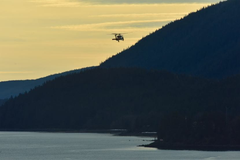 A Coast Guard Air Station Sitka MH-60 Jayhawk helicopter crew searches Gastineau Channel in Juneau on Dec. 6, 2017. Two men remain unaccounted for after their skiff capsized the night before.