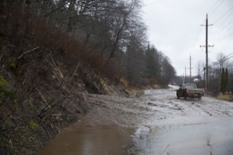 A truck drives through an open lane after a mudslide on Monday, Dec. 11, 2017, in Juneau. The slide happened near the intersection of Mill Street and Thane Road south of downtown Juneau. (Photo by Rashah McChesney/Alaska's Energy Desk)