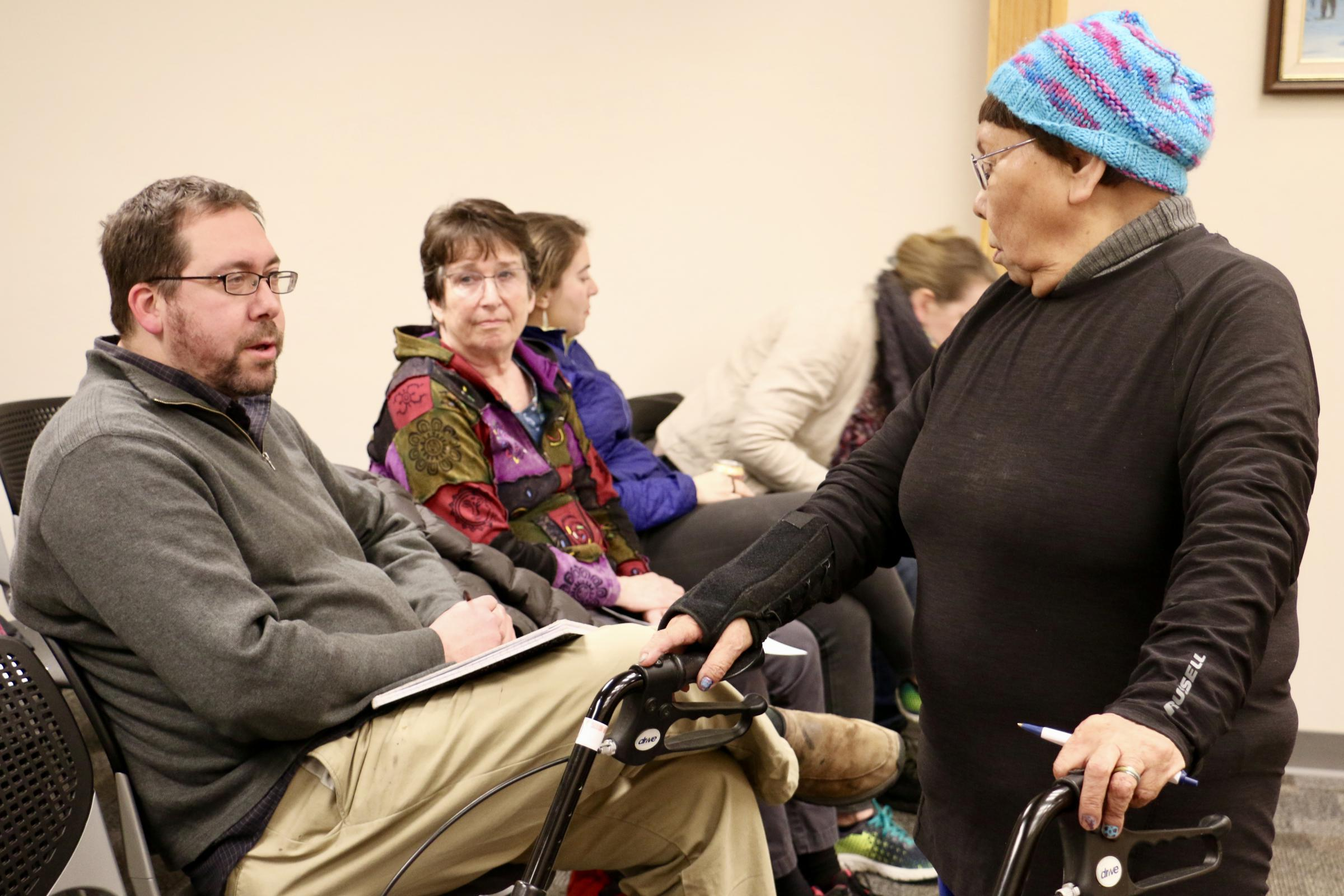 District 38 Representative Zach Fansler speaking with Bethel resident Mary Nanuwak at the December 12, 2017 Bethel City Council meeting. Fansler is accused of hitting a woman when she tried to leave his hotel room. (Photo by Christine Trudeau/KYUK)
