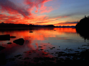 The sun set casts brilliant red light at Lena Beach in Juneau on July 31, 2017.