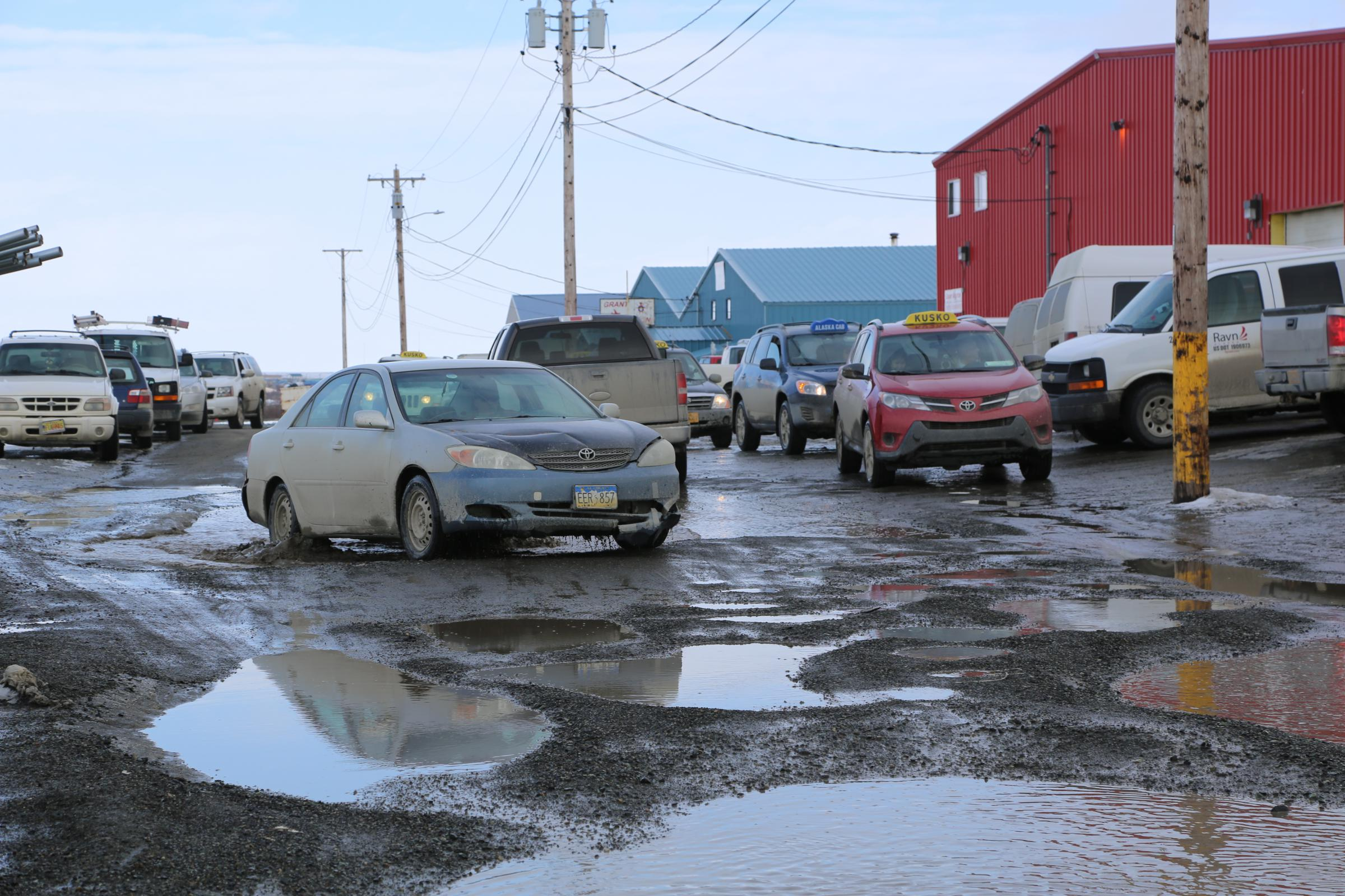 Drivers navigate the potholed road March 28, 2018, in front of the Ravn Air terminal, Bethel. (Photo by Amara Freeman/KYUK)