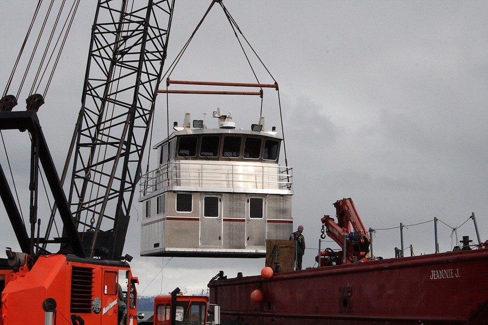 A crane moves an aluminum replacement cabin made by Homer's Bay Weld Boats. The company is one of a number of Alaska businesses already affected by President Trump's imported metals tariffs.